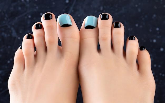 Piedi di womans su sfondo scuro. bellissimo design per unghie blu e nero primavera estate. manicure, concetto di salone di bellezza pedicure.