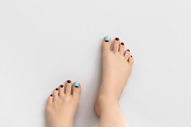 Piedi di donna su sfondo grigio. bellissimo design per unghie blu e nero primavera estate. manicure, concetto di salone di bellezza pedicure.