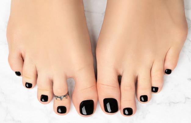 Piedi di donna su sfondo marmo. bellissimo design classico delle unghie nere. manicure, concetto di salone di bellezza pedicure.