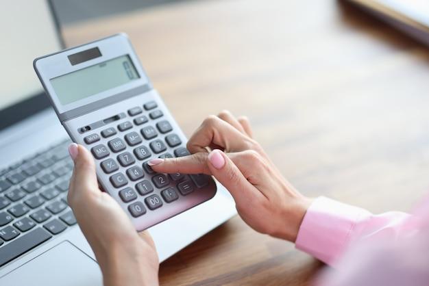 Il dito della donna preme il pulsante sul primo piano della calcolatrice