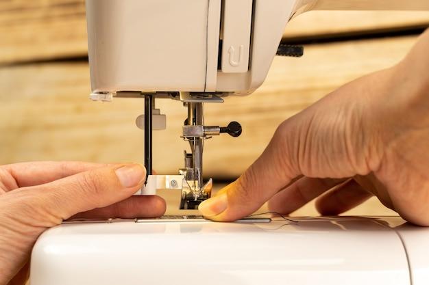 Dita della donna che mette il filo nel cappio dell'ago sulla moderna macchina da cucire elettrica per iniziare a cucire