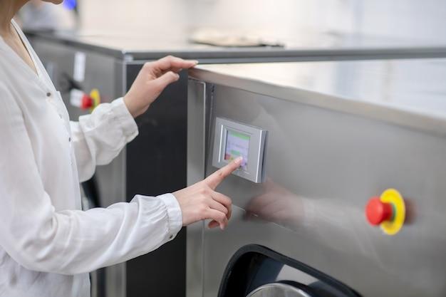 La mano della donna tocca delicatamente il pannello della lavatrice, controllando il suo programma, senza volto