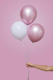La mano della donna tiene tre palloncini rosa e bianchi isolati su sfondo rosa con spazio per il testo