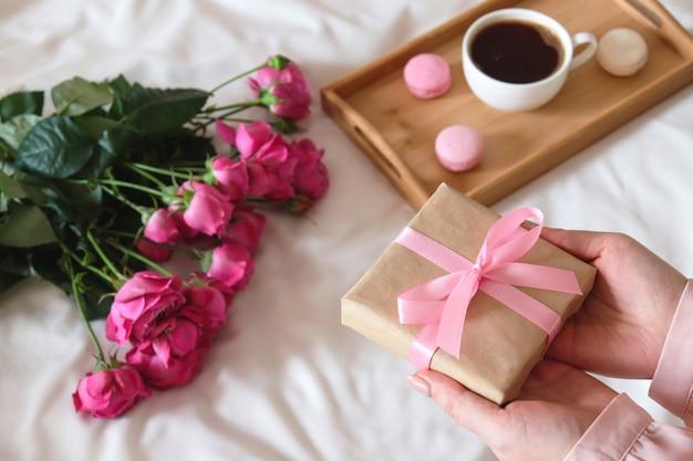 Mano della donna che tiene un regalo composizione accogliente di mattina di festa con rose e tazza di caffè con amaretti sul vassoio di legno