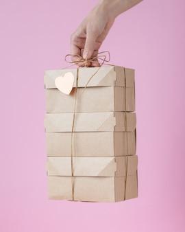 Mano della donna che tiene una scatola di cartone kraft donna che tiene in mano scatole di colore naturale con nastro regalo giallo