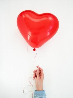 Mano di womans che tiene un palloncino a forma di cuore rosso su bianco