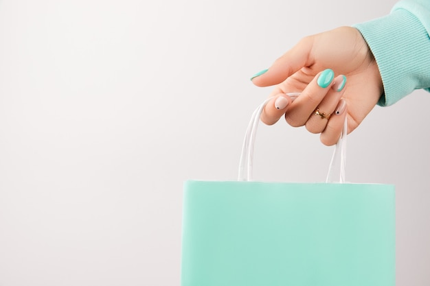Mano della donna che tiene il sacchetto della spesa sopra priorità bassa bianca. design delle unghie turchese. concetto di vendita di moda di bellezza