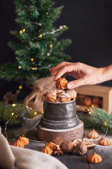 La mano della donna tiene il biscotto picci - biscotti di pasta frolla di natale in vaso vintage su sfondo di rami di abete.