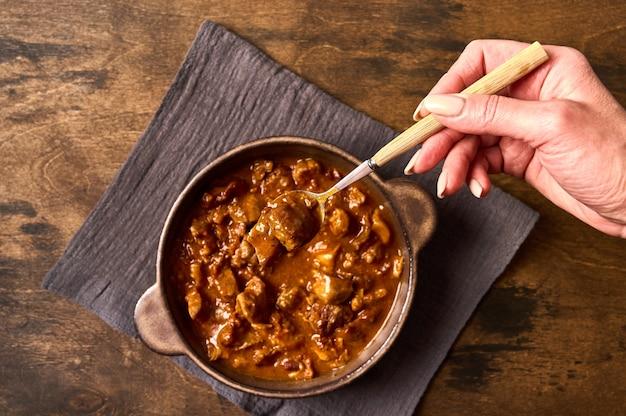 La mano della donna tiene una forchetta con carne di gulasch tradizionale in una ciotola di ceramica sulla vista dall'alto del tovagliolo