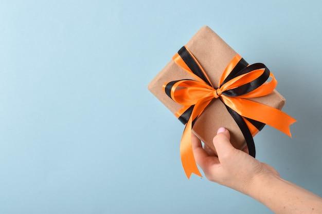 La mano di una donna tiene una confezione regalo con un nastro nero-arancio su sfondo blu