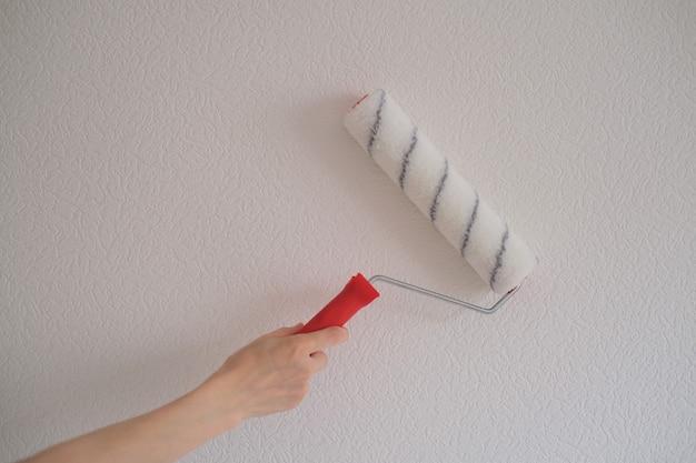 La mano di una donna tiene un rullo con la vernice sullo sfondo di un muro bianco