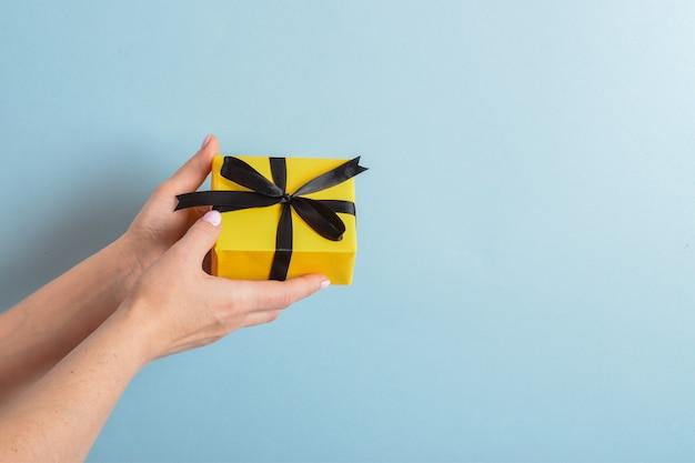 La mano di una donna tiene una confezione regalo gialla con un nastro nero su sfondo blu