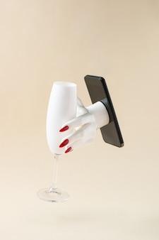 Mano della donna che raggiunge dal telefono che tiene il bicchiere di champagne