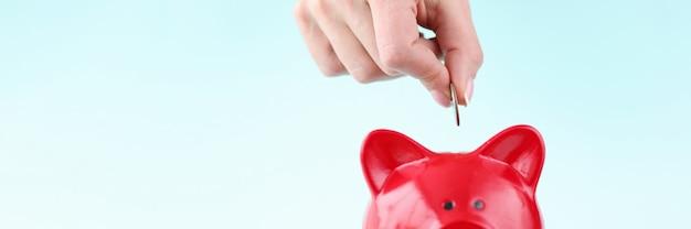 La mano della donna che getta moneta nel primo piano rosso del salvadanaio risparmiando denaro concept