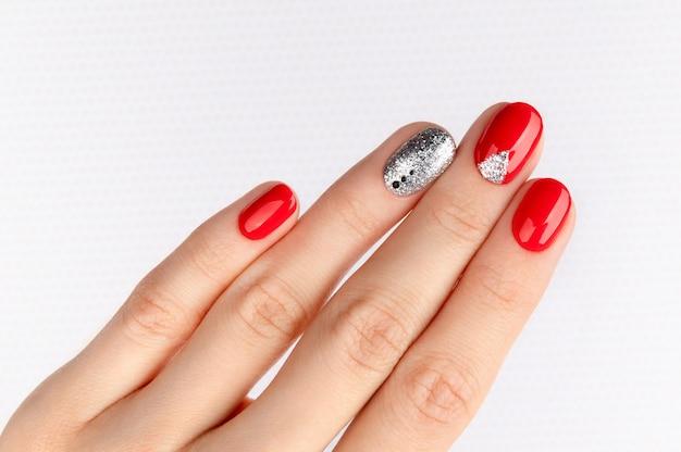 Mano della donna con il manicure rosso alla moda.