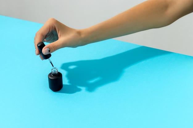 Mano di donna con nail design nudo e blu che tiene una bottiglia di vernice