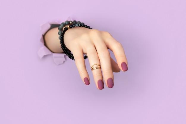 Mano di donna con manicure opaca viola attraverso il foro nel fondo della carta. nail design alla moda primavera estate.