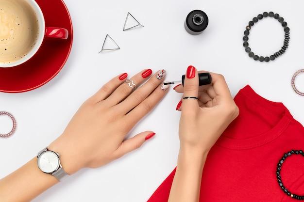 La mano della donna con la manicure rossa che tiene una bottiglia di smalto per unghie