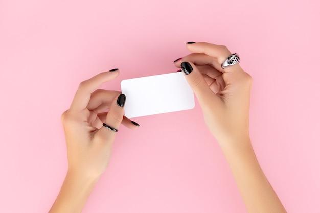La mano della donna con la manicure alla moda che tiene il biglietto da visita sul rosa