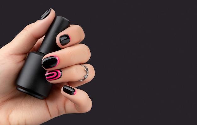 La mano della donna con la manicure alla moda che tiene lo smalto per unghie