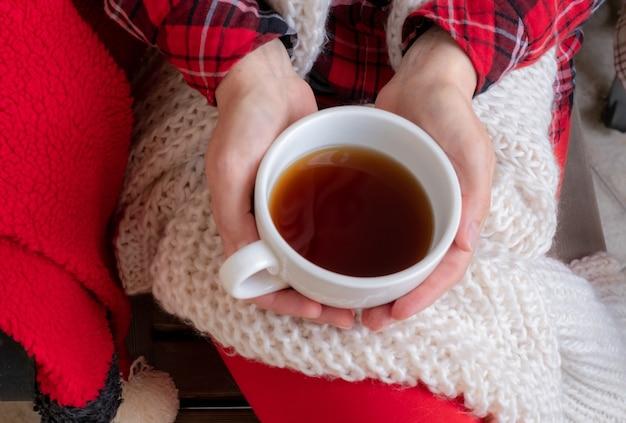 Le mani della donna stanno tenendo la tazza bianca di tè o caffè vestita in vestiti festivi rossi e bianchi