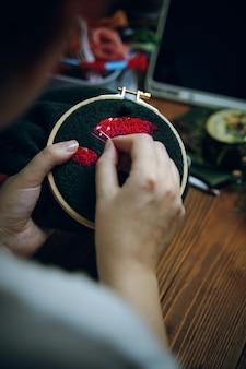 Womans mani ricamo fungo cappello sul telaio ragazza cucito su panno verde concetto di hobby needlewo...