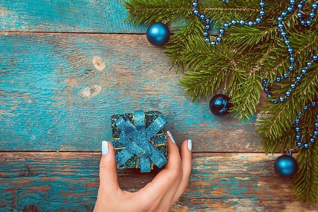 Mani della donna che tengono il contenitore di regalo decorato di natale o capodanno sopra la vista superiore del fondo decorato di natale