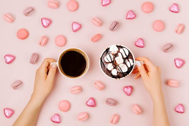 Le mani della donna che tengono tazza di caffè e cioccolata calda con marshmallow su sfondo rosa pallido