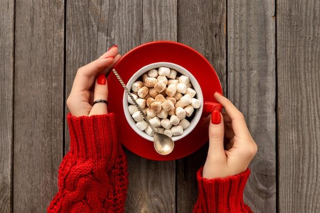 Mani di donna che tengono cioccolata calda con marshmallow in tazza rossa sulla tavola di legno. ricetta del menu della bevanda calda invernale di natale