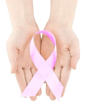 Le mani della donna che tengono il nastro rosa di consapevolezza del cancro al seno, isolato