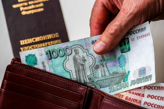 Le mani della donna che tengono il portafoglio con i rubli russi il certificato di pensione russa in background