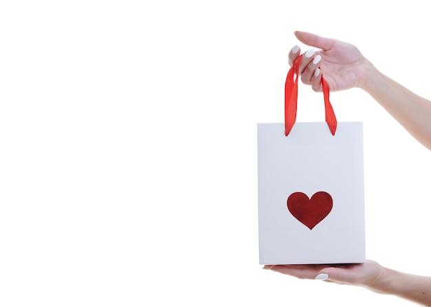 Le mani della donna tengono un pacchetto di carta regalo con un cuore isolato su sfondo bianco.