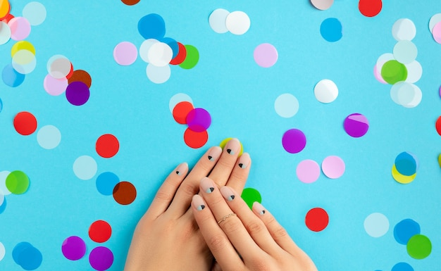 Mani della donna con coriandoli colorati su sfondo blu. concetto di salone di bellezza moda spa