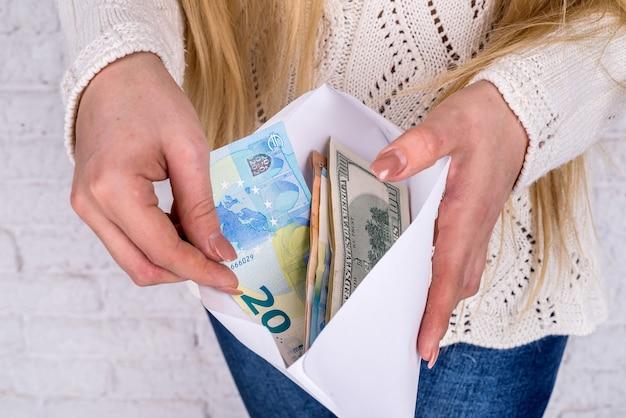 Mani della donna con la busta piena di banconote in dollari ed euro