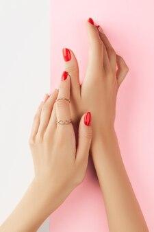 Le mani della donna con la manicure rossa alla moda su sfondo bianco e rosa