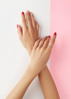 Mani della donna con il manicure rosso alla moda sopra il modello di cura del corpo della stazione termale di trattamento di bellezza della parete bianca e rosa