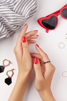 Mani della donna con manicure rossa e accessori moda su sfondo bianco tendenze del design manicure