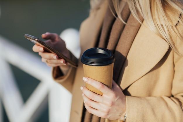Mani della donna con smartphone e caffè Foto Premium