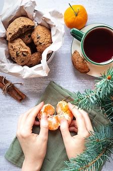 Mani di donna con biscotti al cioccolato al mandarino e un ramo di abete