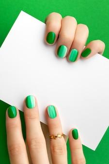 Mani di donna con manicure verde alla moda che tiene la cartolina
