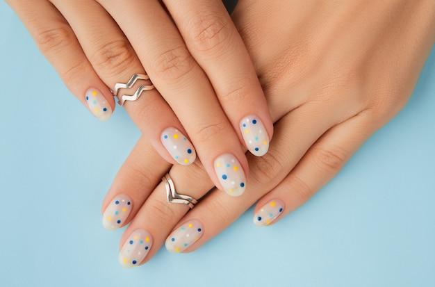 Mani della donna con manicure estiva a pois alla moda su sfondo blu