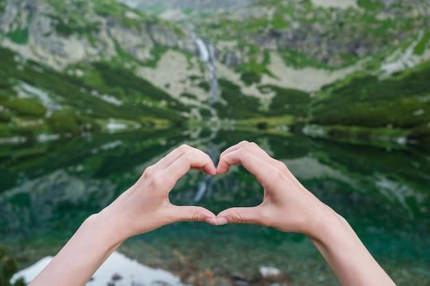 Womans che fa figura del cuore con le sue mani contro le montagne vicino al lago