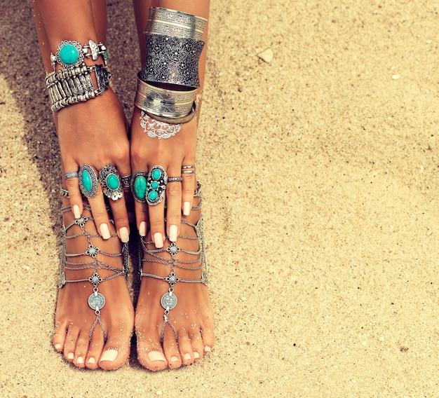 Mani e piedi abbronzati da donna con manicure e pedicure bianche pulite decorate da bracciali e anelli d'argento in stile boho rilassamento sull'invio di una spiaggia tropicale