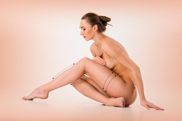Pancia delle donne con le frecce di disegno su di esso su bianco. perdita di grasso, liposuzione e concetto di rimozione della cellulite. collage