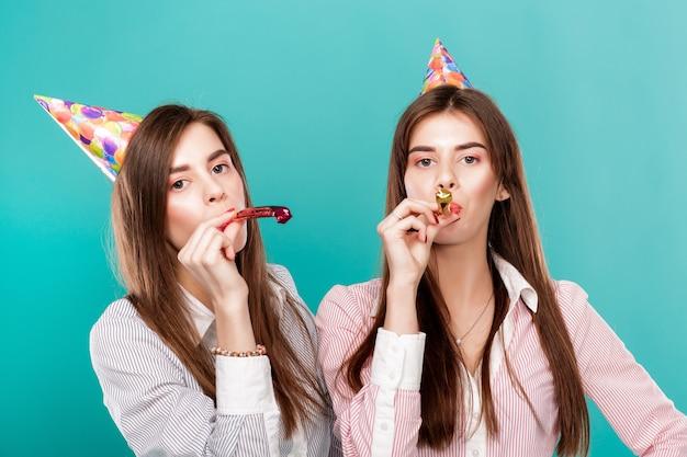 Donne in cappello di compleanno su sfondo blu