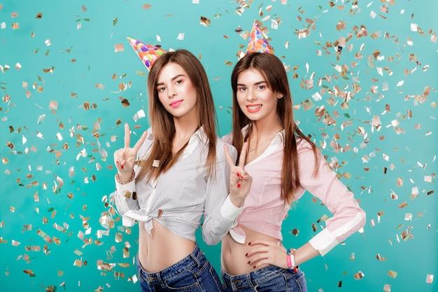 Donne in cappello di compleanno e coriandoli su sfondo blu