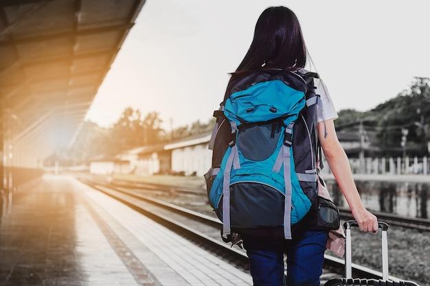 Donne, zaino blu e cappello alla stazione ferroviaria con i turisti. idee di viaggio
