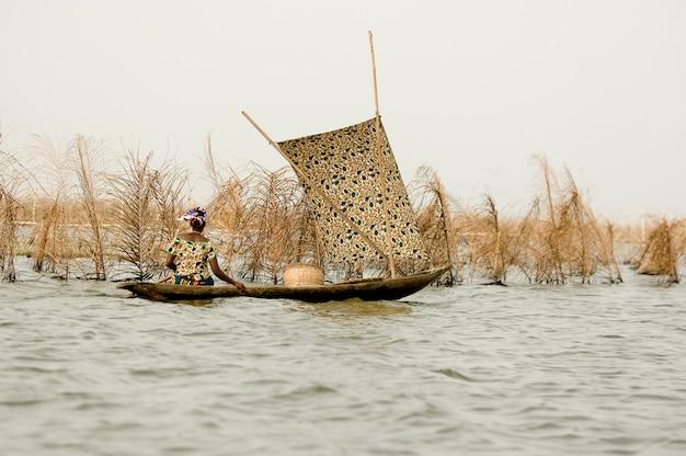 Donne in barca nella laguna del villaggio su palafitte ganvie nel benin.