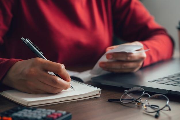 Le donne calcolano le bollette domestiche a casa giovani donne che controllano i costi dell'equilibrio taxtax concept