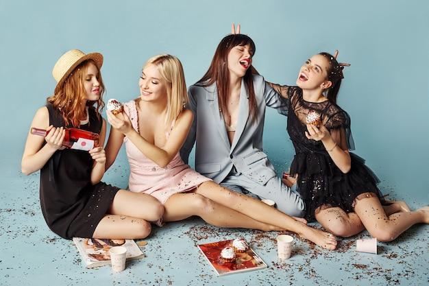 Le donne celebrano la festa divertendosi ridendo e mangiando torte sotto i coriandoli volanti. ragazze in posa e sorridenti su sfondo blu, emozioni allegre, sorrisi e risate